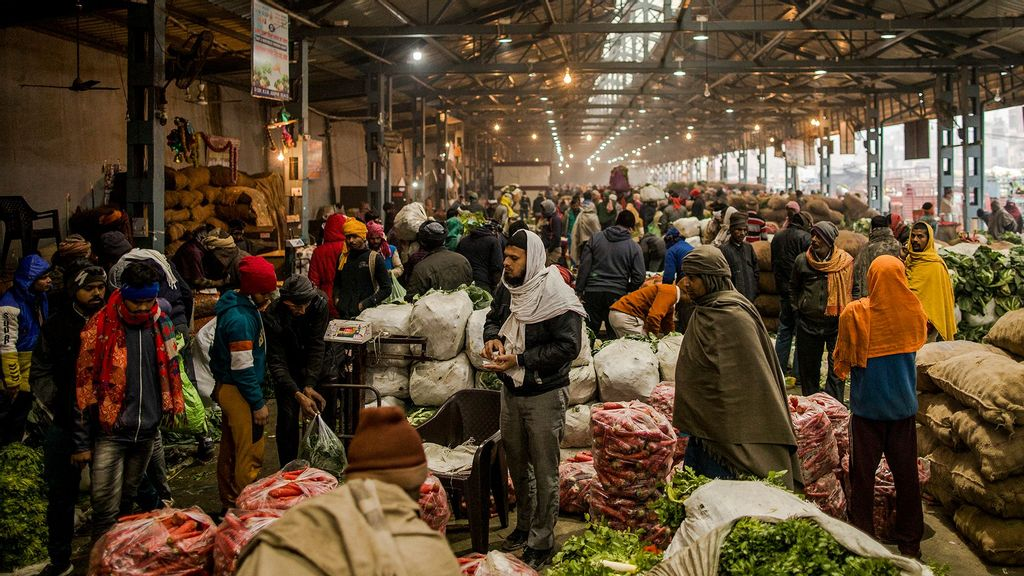 Farmers, commission agents and wholesale buyers mingle as they trade agricultural produce from Bulandshahr at the Azadpur Mandi (wholesale market) on January 17, 2021 in Azadpur, on the outskirts of Delhi, India. (Anindito Mukherjee/Getty Images)